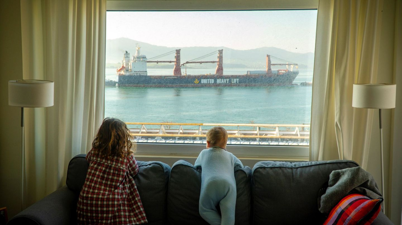 Dos niñas observan desde casa la entrada de barcos mercantes en la bahía de Santander, este miércoles. (EFE)