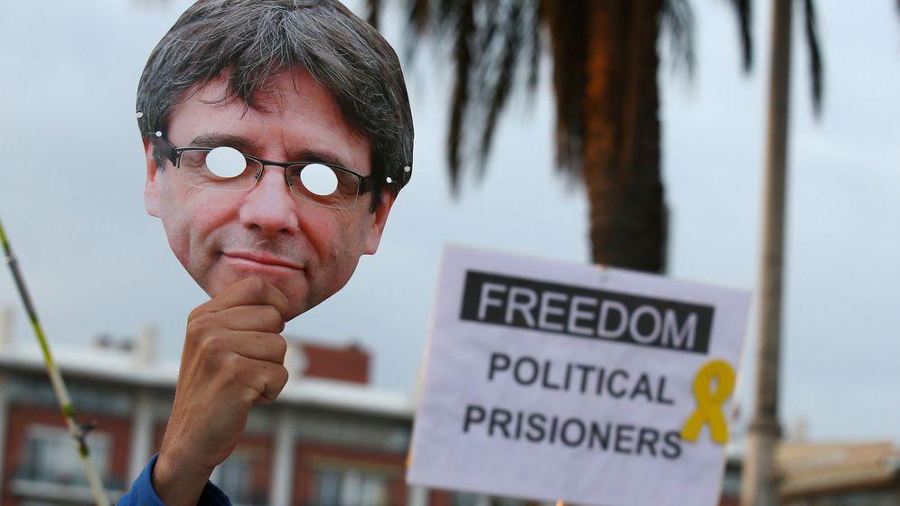 Foto: Un manifestante sujeta una careta de Puigdemont durante una protesta frente al consulado de Alemania en Barcelona. (Reuters)