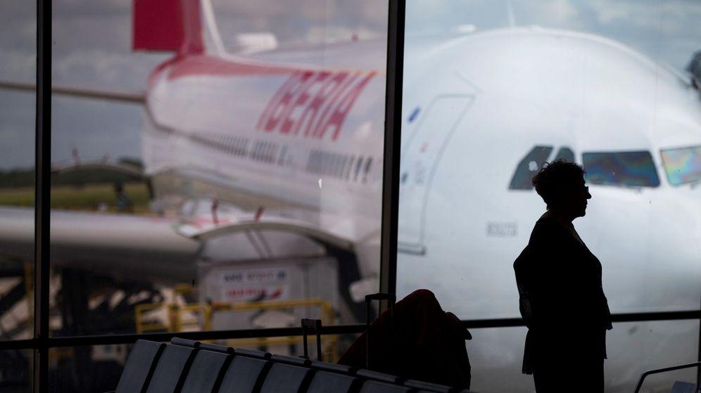 Foto: Una pasajera observa un avión de Iberia estacionado en un aeropuerto. (EFE)