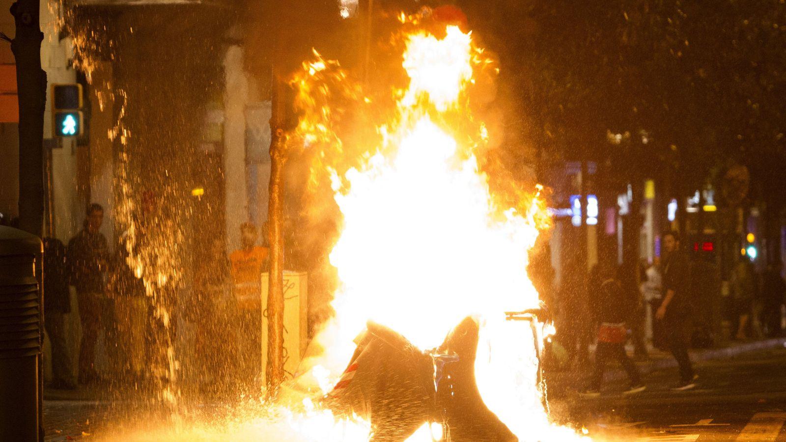 Foto: Varios contenedores han sido incendiados en la calle Gran de Gràcia de Barcelona, tras el tercer día de protestas por el desalojo del 'banco expropiado'. (EFE)