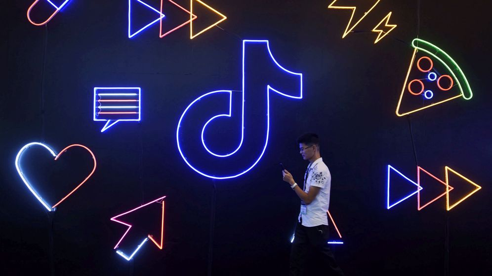 Foto: Un joven en china camina frente al cartel con el logo de la app TikTok. (Reuters)