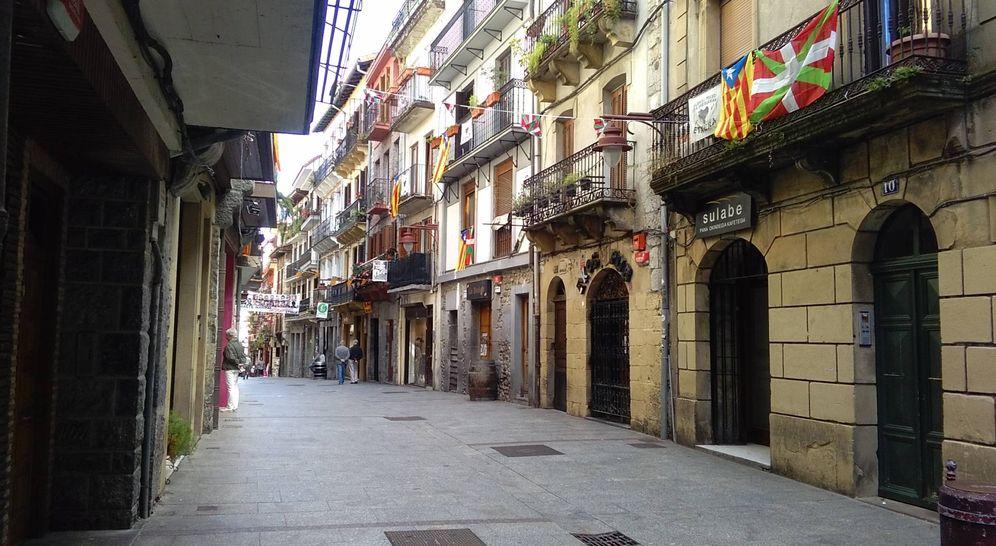 Foto: Una calle de Hernani, con esteladas e ikurriñas en los balcones y banderines de ambas comunidades. Al fondo, una pancarta con los rostros de 20 etarras. (E. C.)