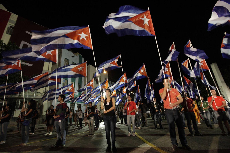Foto: Jóvenes universitarios cubanos sostienen banderas durante el aniversario del nacimiento de José Martí, en la Universidad de La Habana. (Reuters)