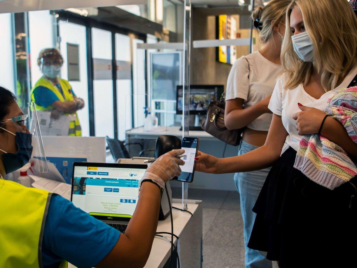 Foto: Pasajeros pasan por un control en el aeropuerto de Mallorca enseñando el certificado covid. (EFE)