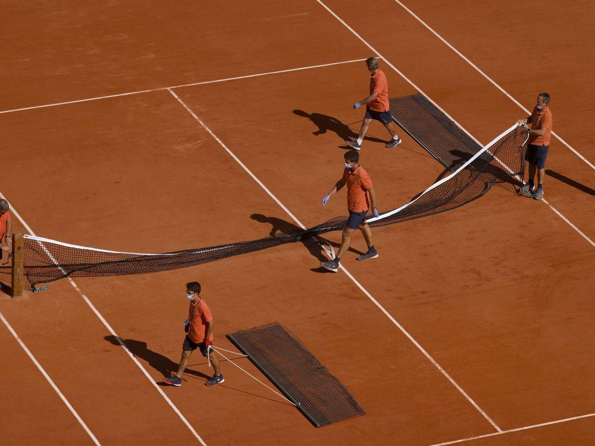Foto: Operarios del torneo preparan la pista central esta semana. (Efe)