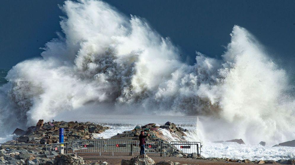 Foto: Una gigantesca ola en la playa de la Barceloneta. (EFE)