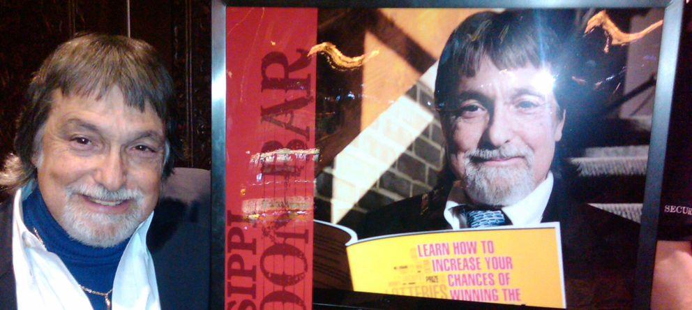 Foto: Richard Lustig posa junto a un cartel que anuncia su libro. (winninglotterymethod.com)