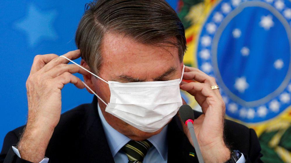 Foto: Bolsonaro poniéndose una mascarilla. (Reuters)