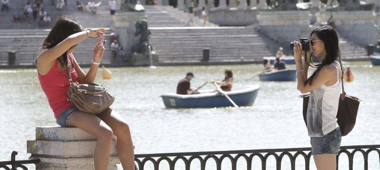Foto: Dos turistas en el Parque del Retiro de Madrid. (EFE)