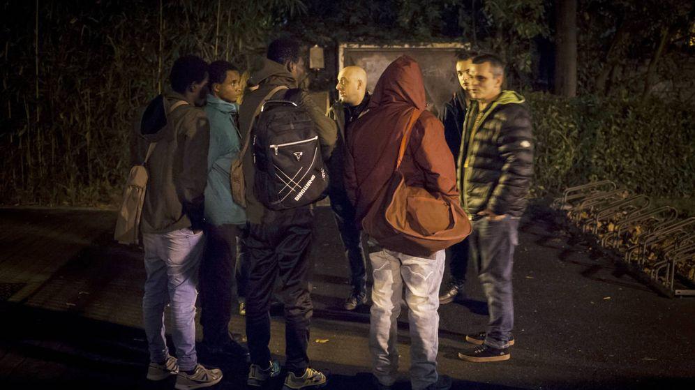 Foto:  Un grupo de voluntarios atiende a varios migrantes a las puertas del centro de acogida Martindozenea. (Gari Garialde / Bostok Photo)