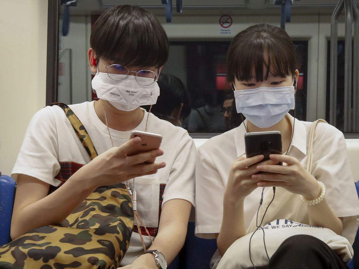 Foto: Dos ciudadanos hongkoneses se protegen del coronavirus. (Reuters)