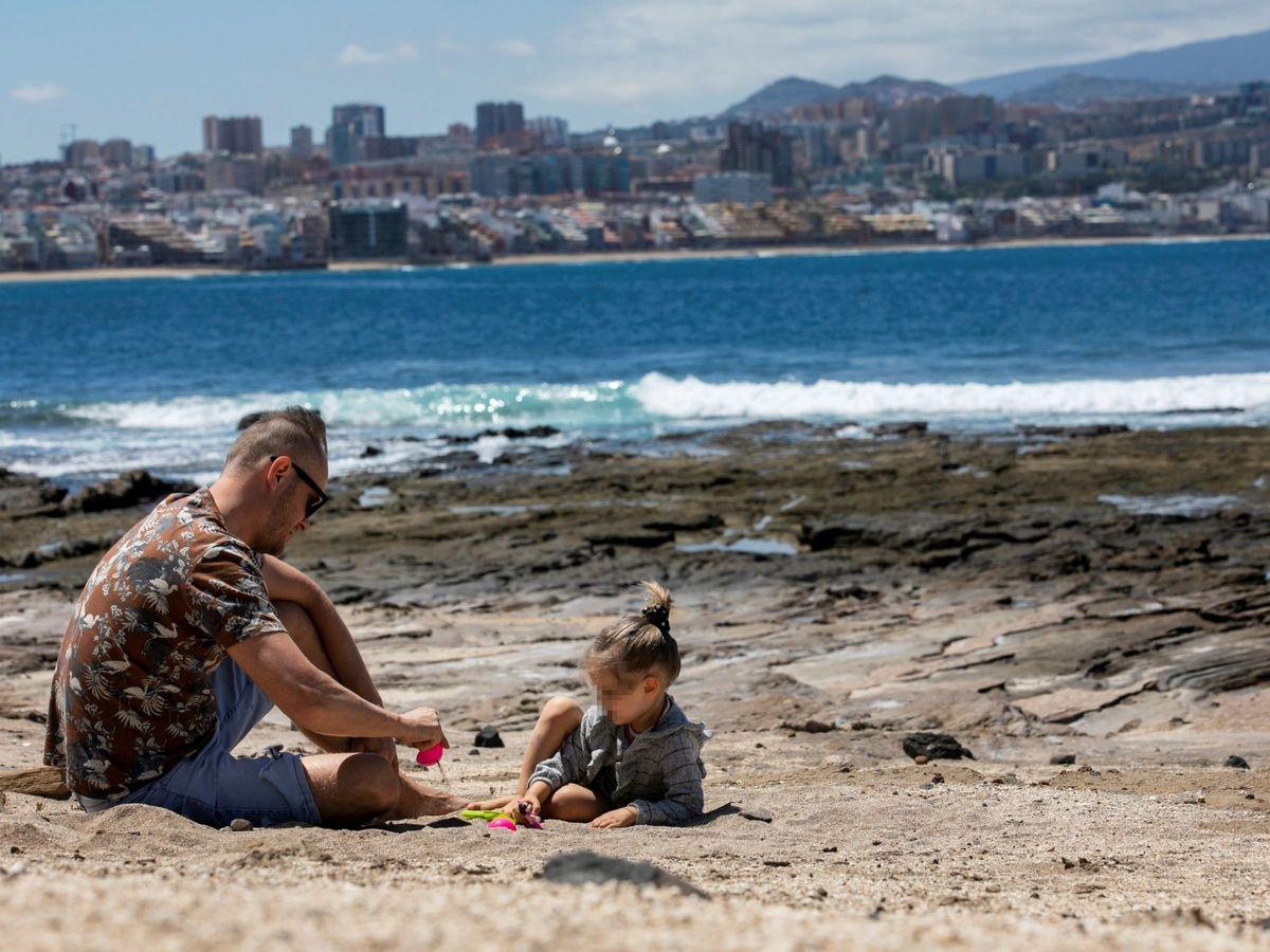 Foto: Un padre y su hija juegan en la playa de El Confital. (EFE)