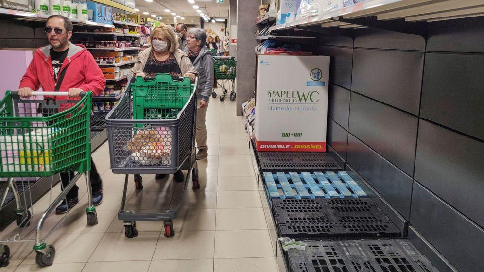 Foto: Una cliente con mascarilla pasa junto a estantes vacíos de papel higiénico en un supermercado de Madrid.  (EFE)