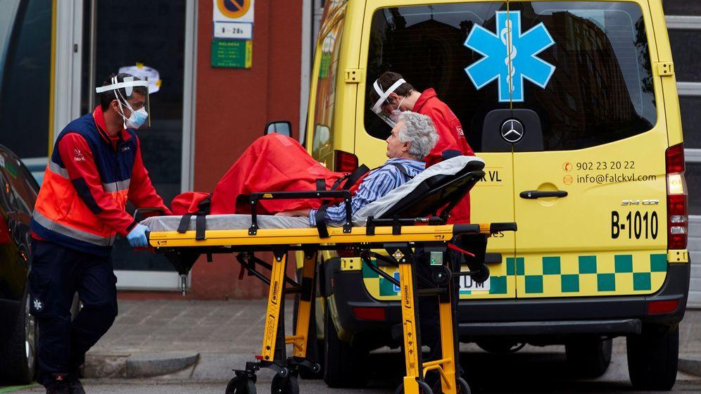 Foto: Operarios de una ambulancia transportan a un enfermo desde su domicilio en el centro de Barcelona. (EFE)