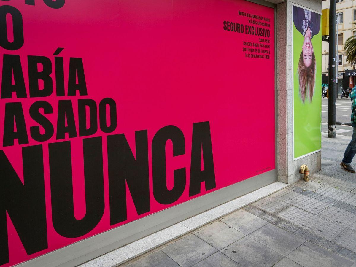 Foto: Un hombre protegido con una mascarilla pasa ante la fachada de una agencia de viajes en Zaragoza. (EFE)