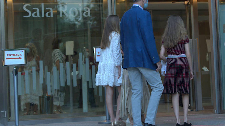 La infanta Sofía, con vestido blanco, y la princesa Leonor, con vestido oscuro, entrando al teatro junto a sus padres. (Limited Pictures)