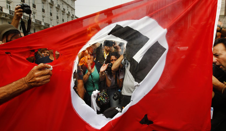 Foto: Manifestantes queman una bandera nazi durante una visita de Angela Merkel a Atenas, en octubre de 2012. (Reuters)