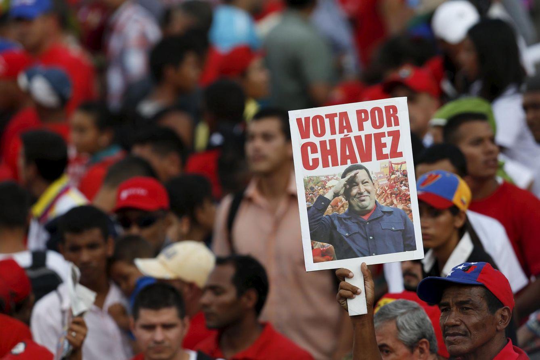 Foto: Un simpatizante de Nicolás Maduro sostiene un cartel de Hugo Chávez durante el evento de cierre de campaña, en Caracas, el 3 de diciembre de 2015 (Reuters).