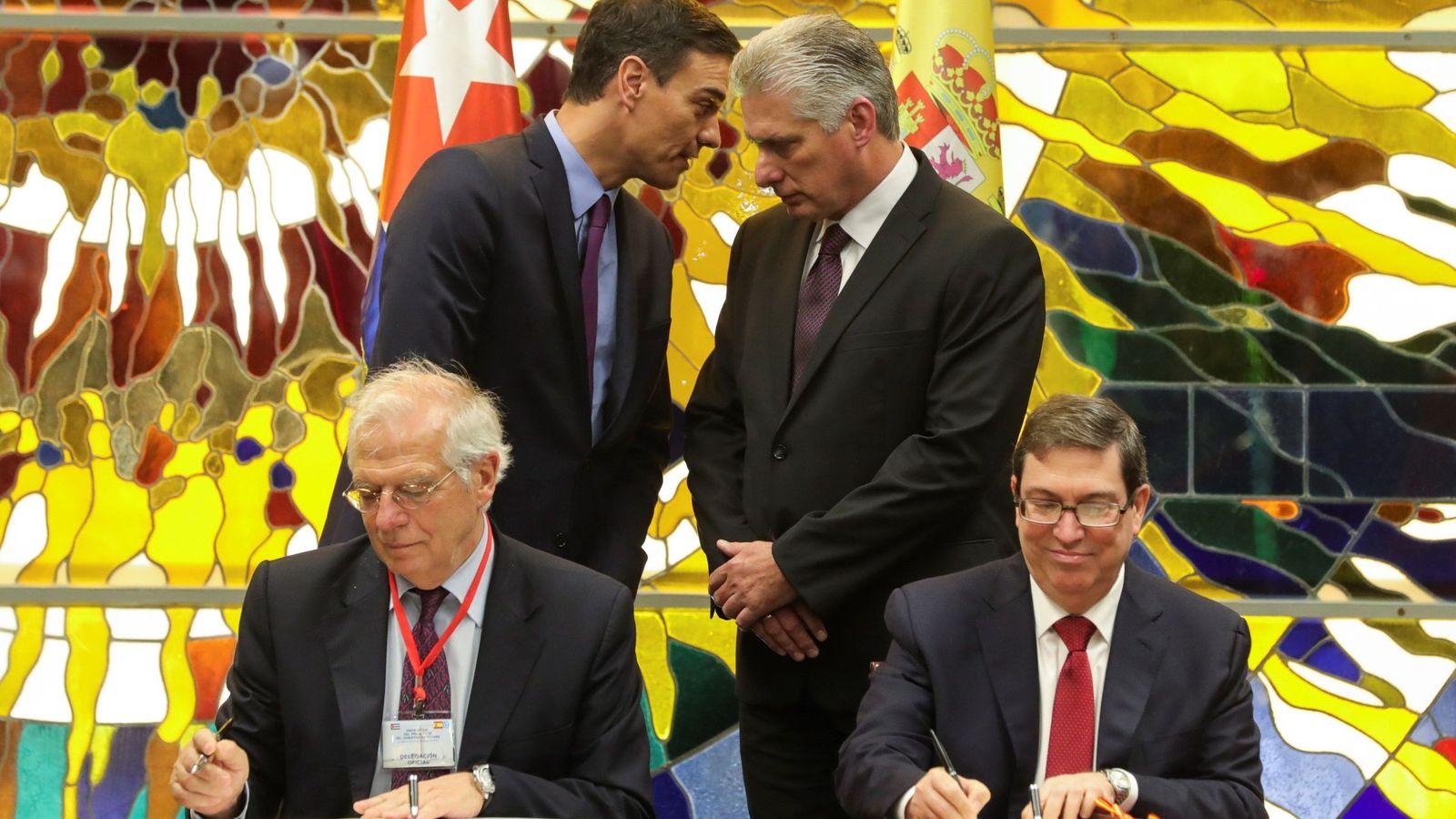Foto: Pedro Sánchez y Miguel Díaz-Canel charlan mientras sus ministros de Exteriores firman uno de los dos acuerdos alcanzados, este 22 de noviembre en La Habana. (EFE)