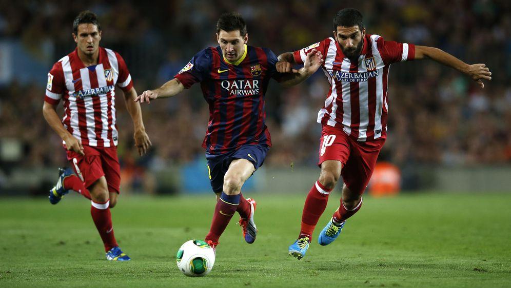 Foto: Arda Turan puja por un balón con Messi, con Koke al fondo, durante un Barcelona-Atlético disputado en el Camp Nou (Reuters)
