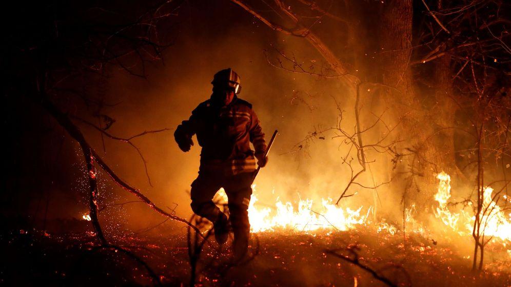 Foto: Los bomberos intentan sofocar el incendio que se ha producido hoy en los alrededores de Labares (Asturias). (EFE)