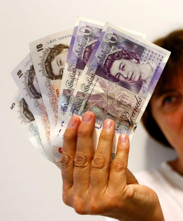 Foto: Una mujer muestra varios billetes de libras. (Reuters)