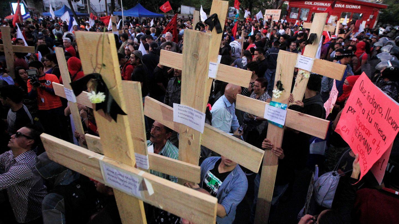 Un grupo de manifestantes carga cruces con los nombres de las víctimas durante las protestas. (Reuters)
