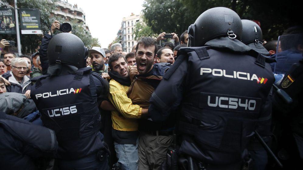 Foto: Agentes antidisturbios de la Policía Nacional forman un cordón de seguridad frente al colegio Ramón Llull de Barcelona el 1-O. (EFE)