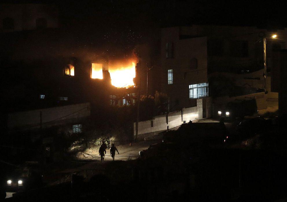 Foto: Soldados israelíes caminan ante las llamas de la casa familiar en Hebrón de un palestino acusado del secuestro de los jóvenes israelíes (Reuters).