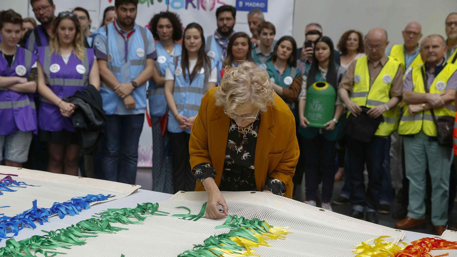 Foto:  La alcaldesa de Madrid, Manuela Carmena, pone lazos de colores durante la presentación  de la bandera arcoíris. (EFE)