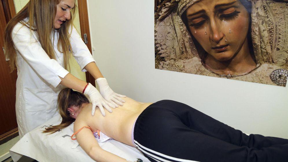 Foto: Una fisioterapeuta da masajes a una costalera en el Centro de Atención al Costalero (CEACO) en Granada. (EFE)