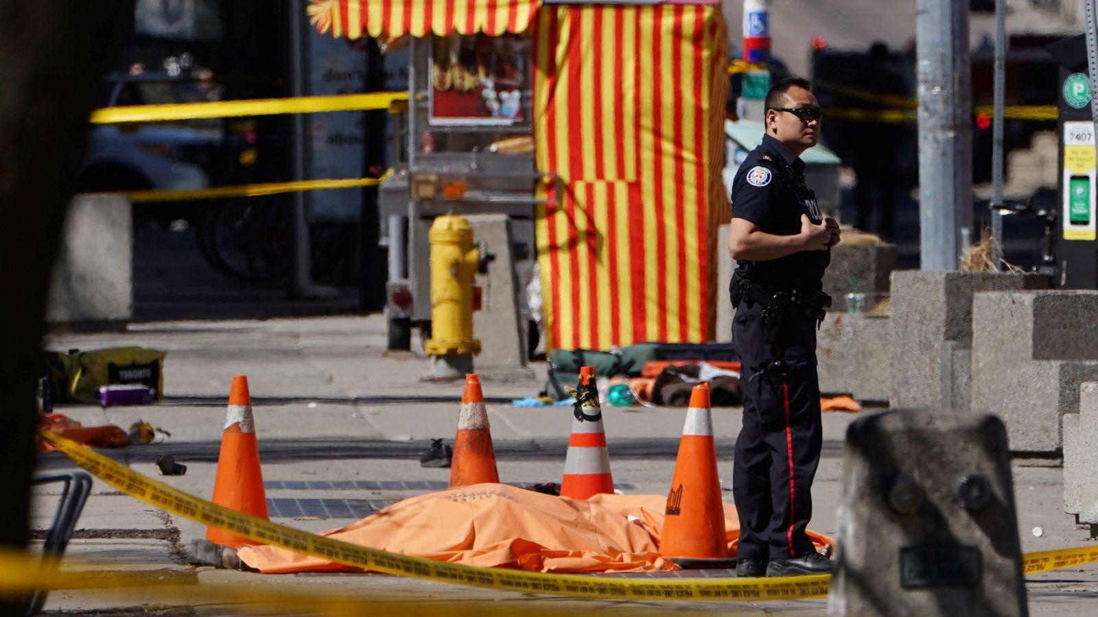 Foto: Un oficial de policía, junto a una de las víctimas del atropello. (Reuters)