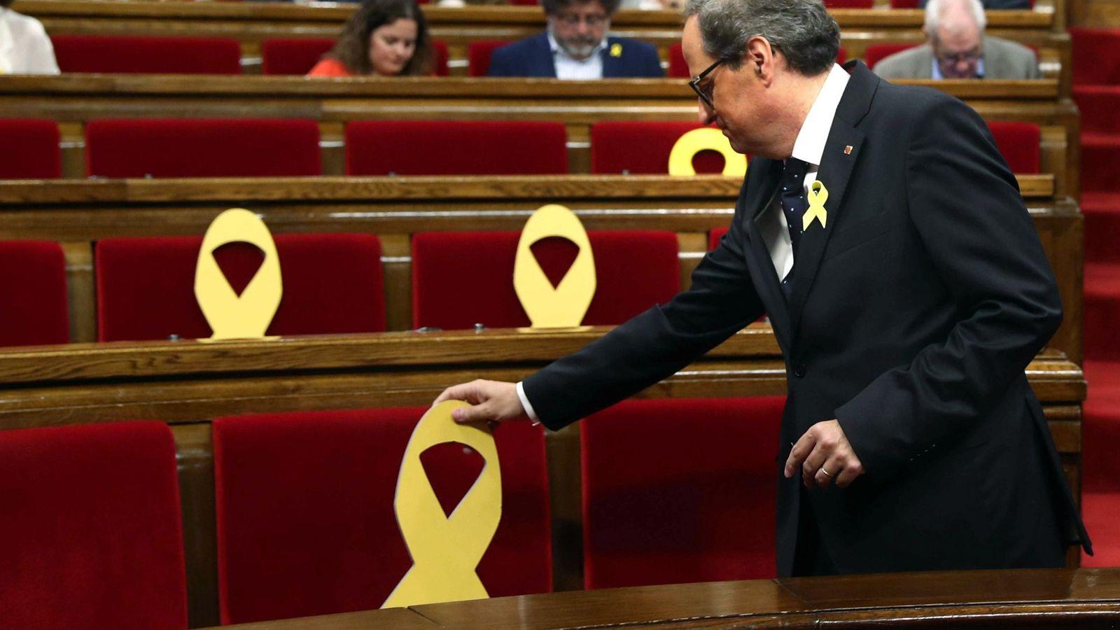 Foto: El presidente de la Generalitat, Quim Torra, coloca un lazo amarillo en uno de los asientos del Parlament. (EFE)