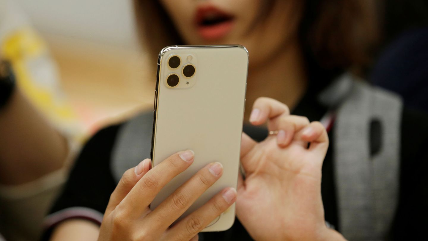 A woman holds an iPhone 11 Pro Max while giving a live broadcast after it went on sale at the Apple Store in Beijing, China, September 20, 2019. REUTERS Jason Lee