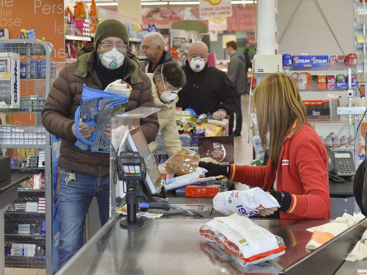 Foto: Personas usan máscaras protectoras mientras compran en un supermercado en Casalpusterlengo, Italia. (EFE)