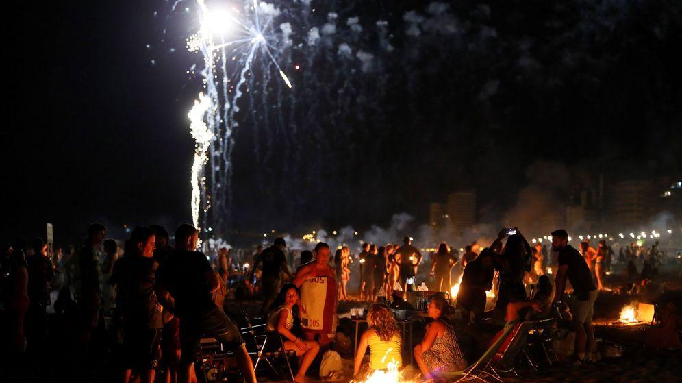 Foto: Numerosas personas disfrutan de la Noche de San Juan en la playa del mismo hombre de Alicante. (EFE)