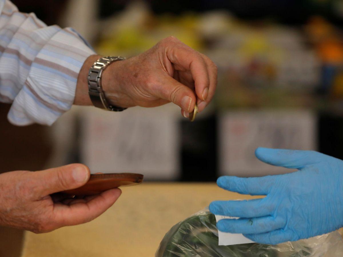 Foto: Un comprador paga a una cajera. (Reuters)