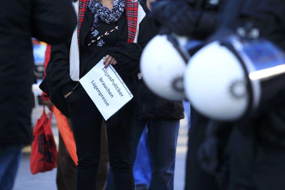 Foto: Una mujer enarbola un cartel que dice Los políticos mentirosos necesitan una prensa mentirosa, durante una marcha de Pegida en Colonia, el 9 de enero de 2016 (Reuters)