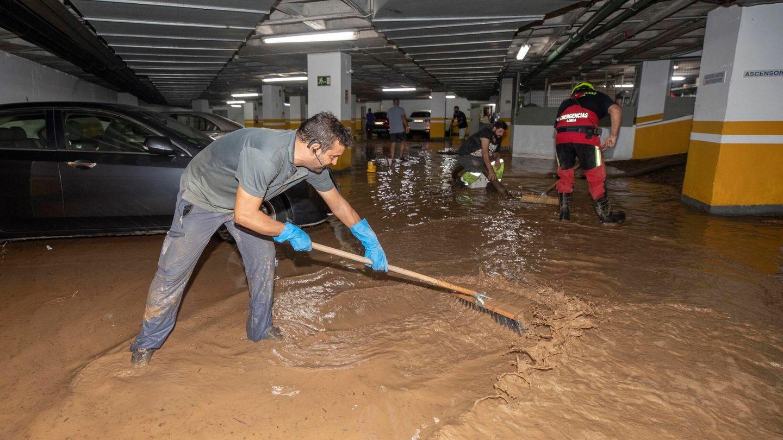 Trabajadores del Ayuntamiento de Águilas achican agua del garaje de un hotel, tras la gota fría de este jueves. (EFE)