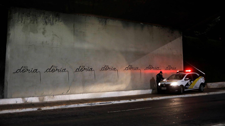 Un coche de policía investiga unas pintadas con el nombre de Doria realizadas por un artista llamado Iaco, en la avenida 23 de Maio de Sao Paulo, en marzo de 2017. (Reuters)