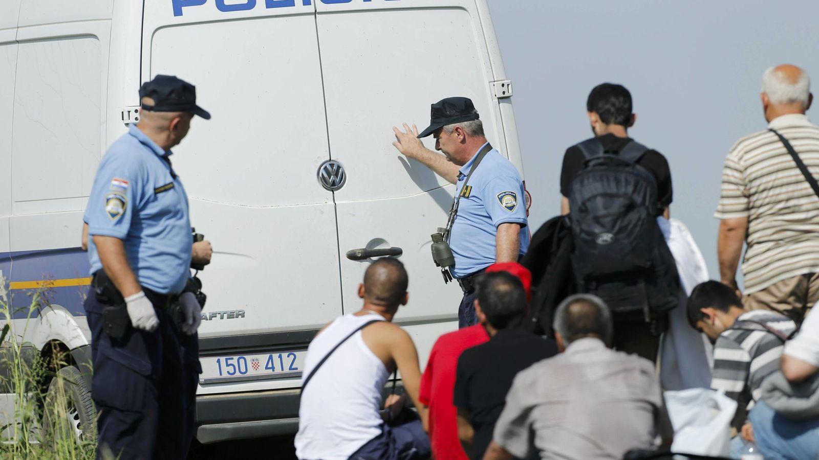 Foto: Un grupo de refugiados, con agentes de la policía croata (Reuters).