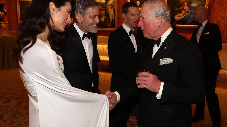 Amal y George Clooney hablando con el príncipe de Gales durante la cena de The Prince's Trust. (Getty)