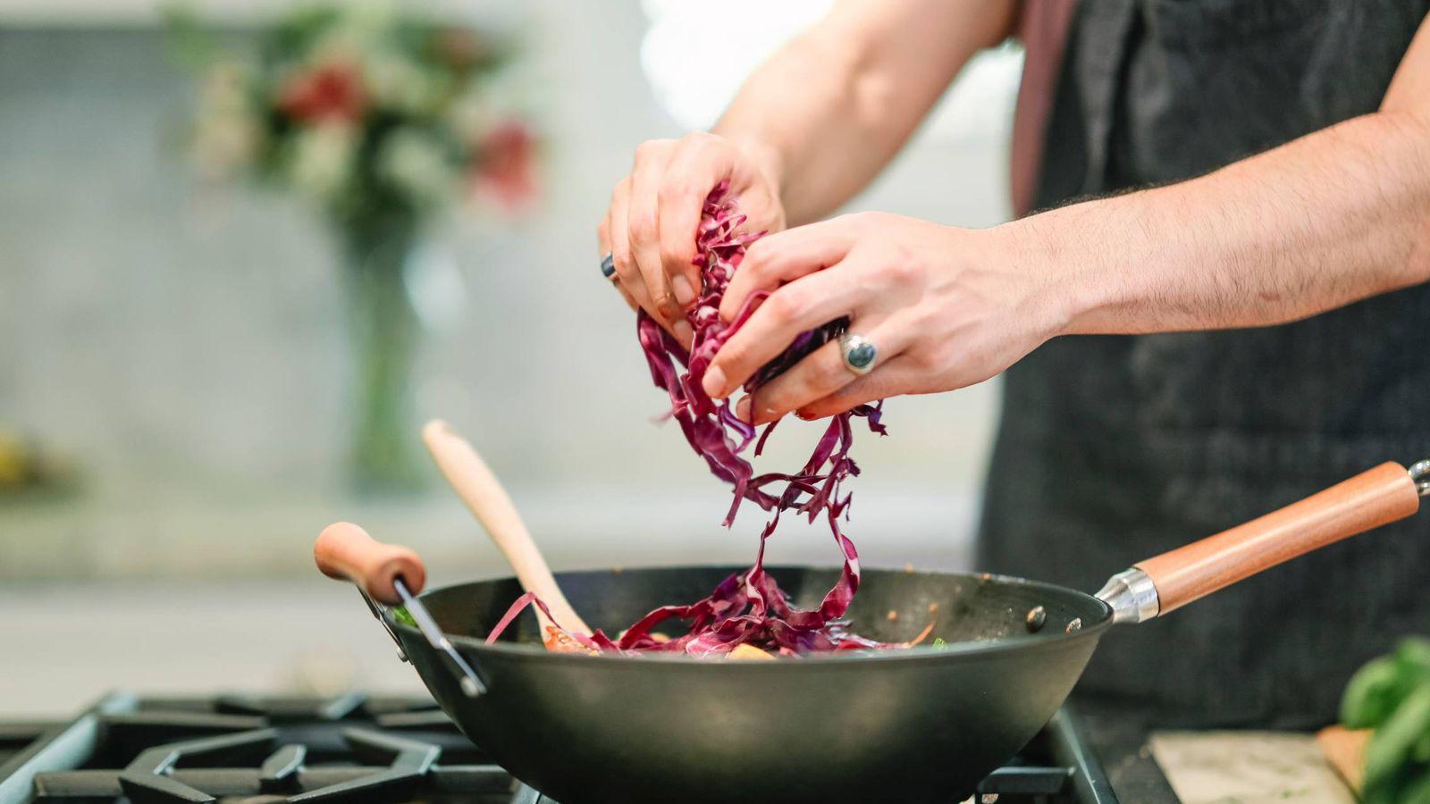 Foto: Un cocinero echa verduras cortadas con un espiralizador en una sartén (Foto: Pexels)