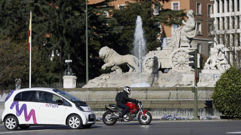 Un coche de alquiler eléctrico de cuatro plazas de la empresa Emov, a su paso por la fuente de Cibeles (Madrid). (EFE)