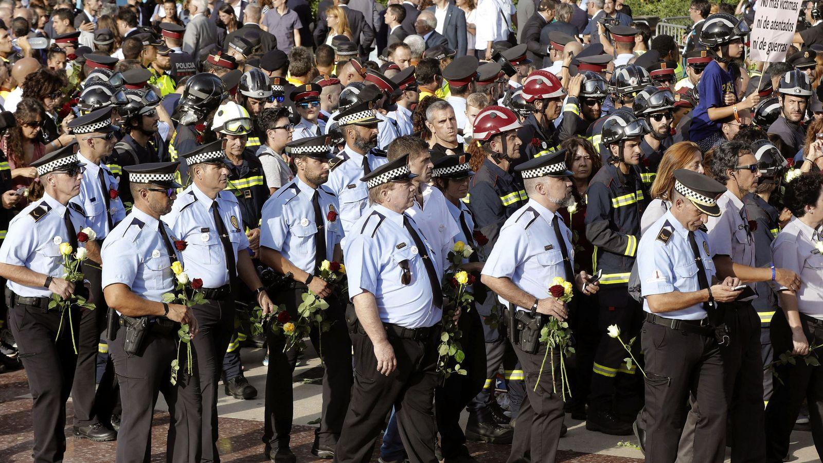 Foto: Miembros de la Guardia Urbana y los Bomberos de Barcelona portan rosas durante la manifestación contra los atentados yihadistas en Cataluña. (EFE)