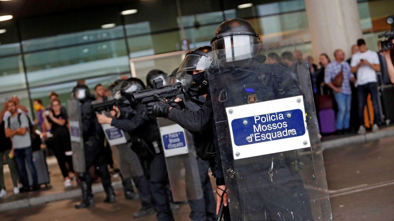 Miembros de los Mossos controlan a las centenares de personas que se agolpan ante el Prat.