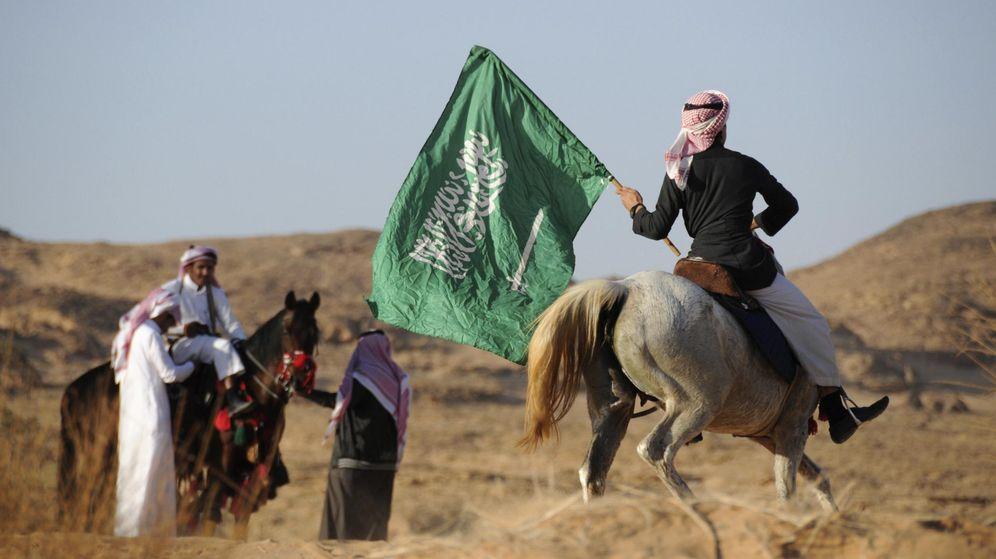 Foto: Un hombre a caballo ondea la bandera nacional de Arabia Saudita. (Reuters)