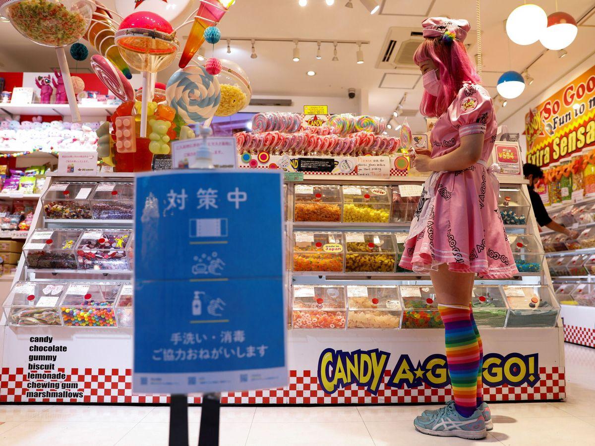 Foto: La empleada de una tienda de dulces trabaja frente a un cartel de medidas de prevención contra el covid-19. (Reuters)