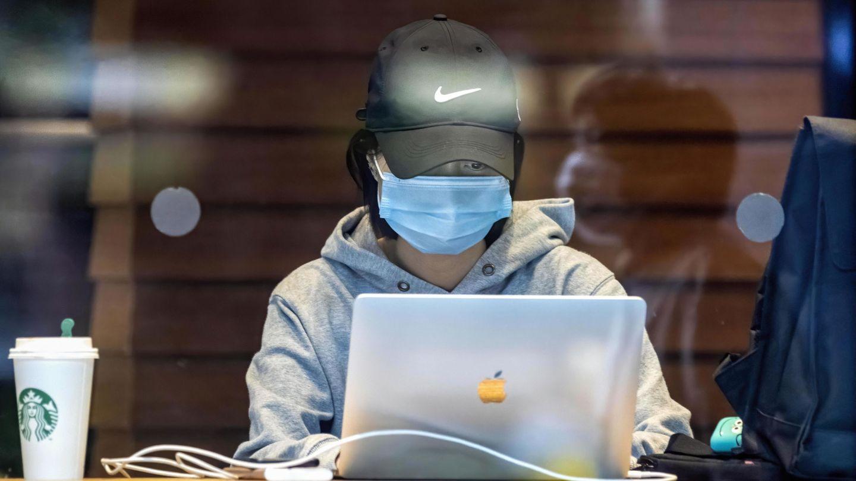 Una mujer con mascarilla se conecta en un Starbucks en Guangzhou, China. (Reuters)