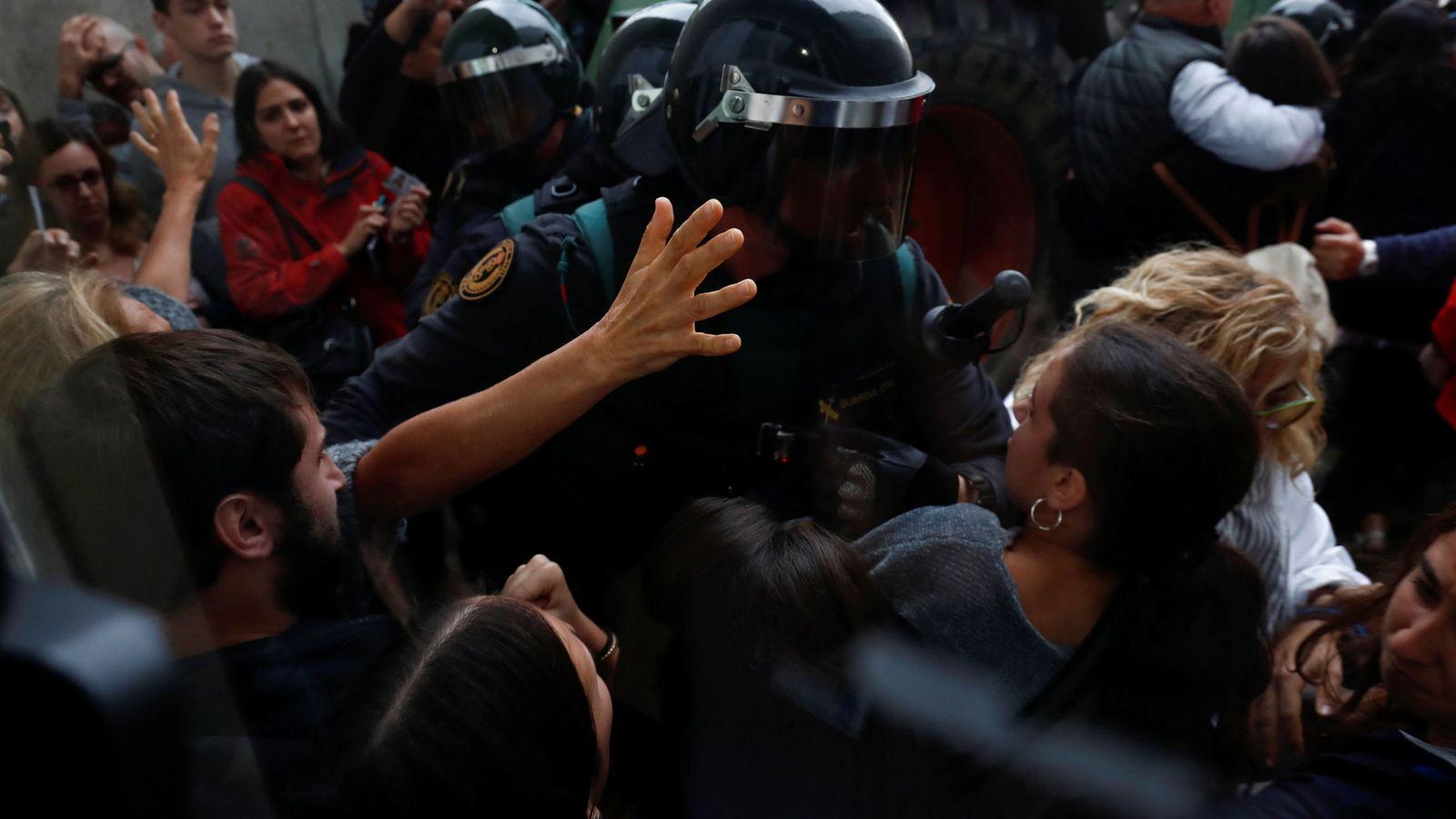 Foto: Un policía increpa a una ciudadana en el colegio donde iba a votar Carles Puigdemont. (Reuters)